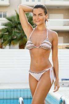 Mulher com corpo bonito ao lado de uma piscina