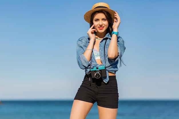 Mulher com corpo bronzeado, lábios carnudos e pernas longas, posando na praia tropical ensolarada. vestindo top crop, shorts e chapéu de palha.