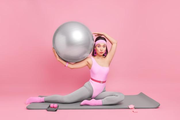 Mulher com corpo em forma faz exercícios aeróbicos sendo instrutora de fitness trabalha no centro de treinamento segura bola de pilates vestida com roupas esportivas