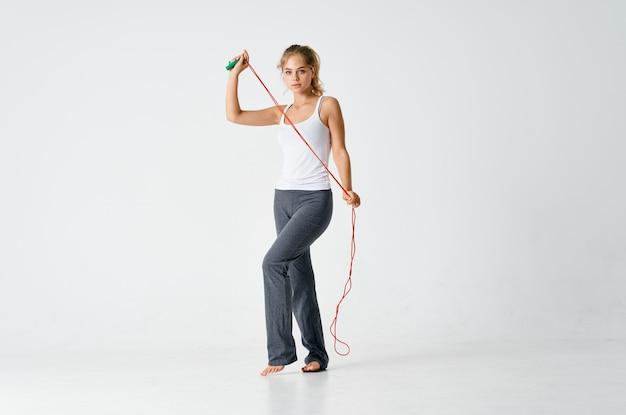 Mulher com corpo esguio malhando em uma academia de ginástica para pular corda