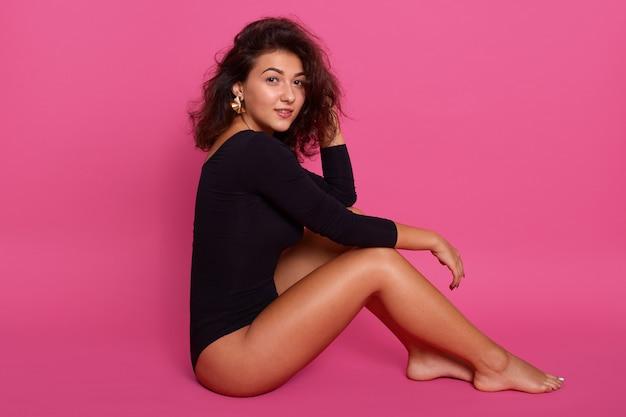 Mulher com corpo perfeitamente moldado, sentada no chão e segurando uma mão na perna dela e tocando seus cabelos escuros ondulados com outra, a garota veste o preto combidress