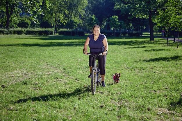 Mulher com corpo positivo andando de bicicleta no jardim com yorkshire terrier