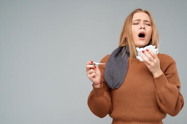 Mulher com corrimento nasal está prestes a espirrar em um guardanapo.