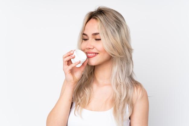 Mulher com cosméticos sobre parede isolada