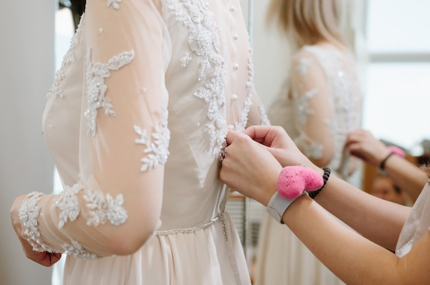 Mulher com costureira fazendo o toque final na loja de roupas de noiva
