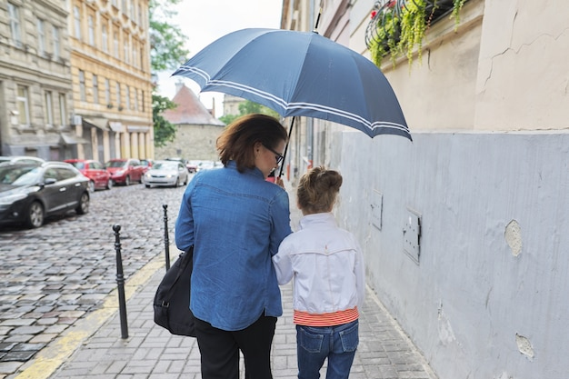 Mulher com criança menina andando sob um guarda-chuva na rua