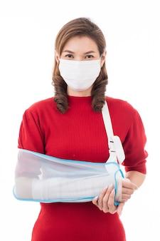 Mulher com curativo no braço e máscara