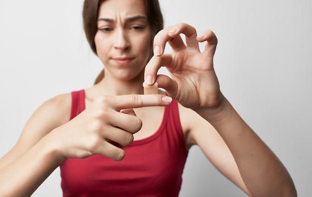Mulher com dedo quebrado vestindo camiseta vermelha com ferimento em problemas de saúde