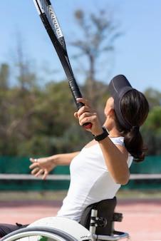 Mulher com deficiência de tiro médio jogando tênis