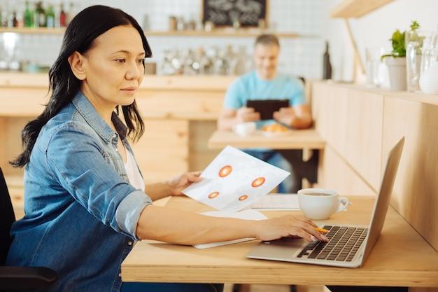 Mulher com deficiência e cabelos escuros muito concentrada, sentada em uma cadeira de rodas, segurando uma folha de papel, trabalhando em seu laptop e um homem sentado ao fundo