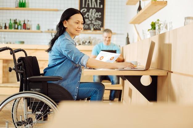 Mulher com deficiência e cabelos escuros, muito sorridente, sentada em uma cadeira de rodas, segurando uma folha de papel e trabalhando em seu laptop em um café