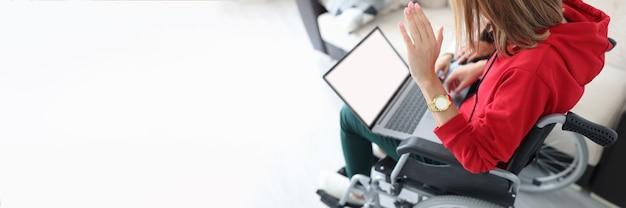 Mulher com deficiência em cadeira de rodas acenando com a mão para a tela do laptop
