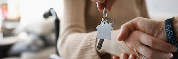 Mulher com deficiência em cadeira de rodas apertando a mão de um homem com as chaves do novo apartamento.