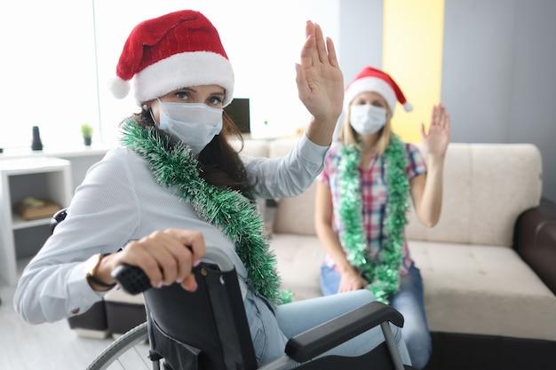 Mulher com deficiência em cadeira de rodas com chapéu de papai noel vermelho acenando com a mão no fundo de uma amiga