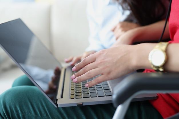 Mulher com deficiência em cadeira de rodas digitando no teclado do laptop close-up
