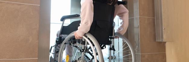 Mulher com deficiência em cadeira de rodas entrando na vista traseira do elevador
