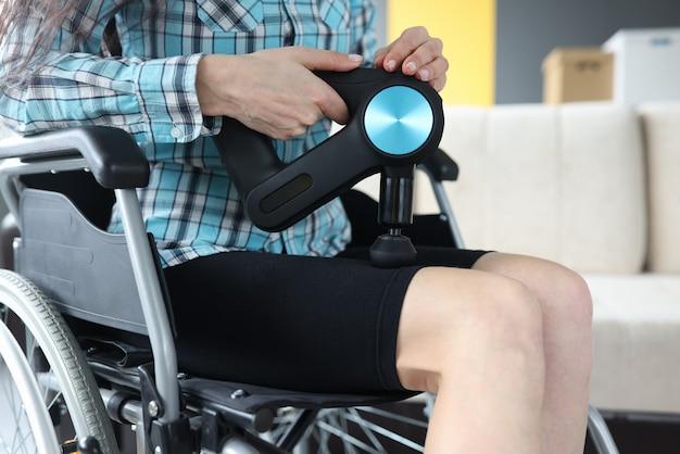 Mulher com deficiência em cadeira de rodas fazendo massagem nas pernas com massageador de percussão closeup