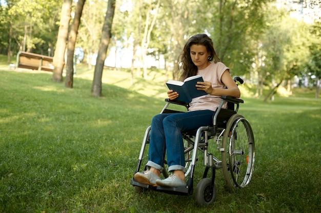 Mulher com deficiência em cadeira de rodas, lendo um livro no parque. pessoas paralisadas e incapacitadas, superação de deficiências. de lazer para deficientes físicos ao ar livre