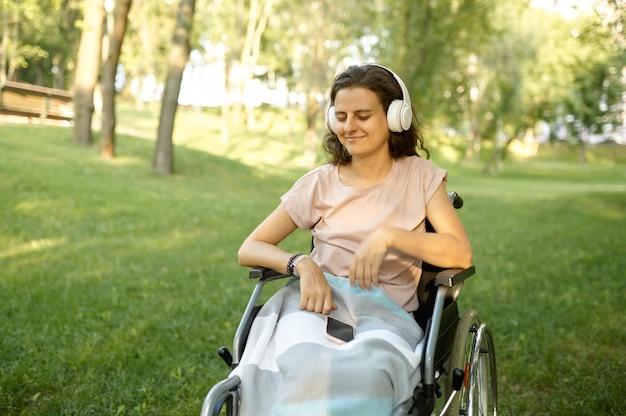 Mulher com deficiência em cadeira de rodas ouve música com fones de ouvido no parque. pessoas paralisadas e incapacitadas, superação de deficiências. mulher com deficiência caminhando no parque