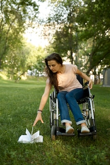 Mulher com deficiência em cadeira de rodas tenta pegar um livro caído no parque. pessoas paralisadas e incapacitadas, superação de deficiências. de lazer para deficientes físicos ao ar livre