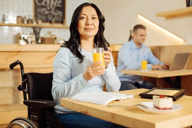 Mulher com deficiência muito vigorosa, sentada em uma cadeira de rodas, bebendo suco, olhando à distância e um homem sentado ao fundo