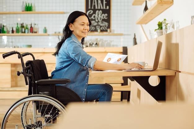 Mulher com deficiência, sorridente e atraente, de cabelos escuros, sentada em uma cadeira de rodas, segurando uma folha de papel e trabalhando em seu laptop em um café