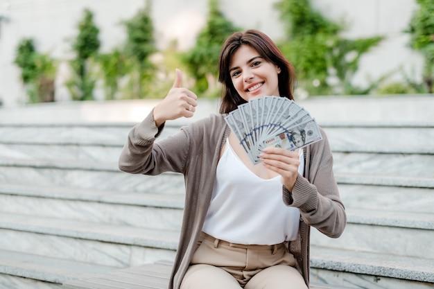 Mulher com dinheiro dólar na mão mostra os polegares para cima