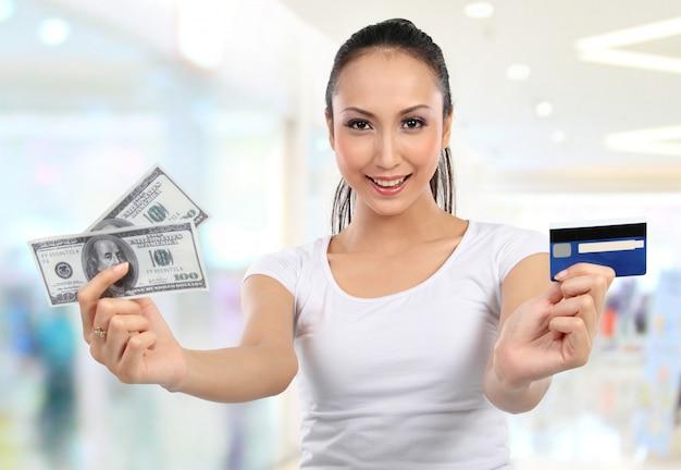 Mulher com dinheiro e cartão de crédito