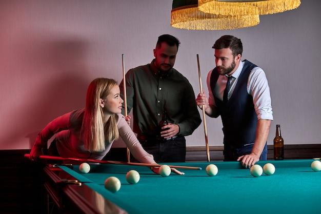Mulher com dois amigos do sexo masculino joga bilhar no bar depois do trabalho, tem tempo de descanso e folga, preparando-se para jogar bolas de bilhar