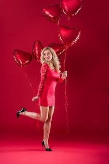 Mulher com dois cachos de balões em formato de coração