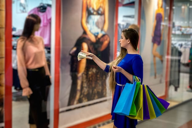 Mulher com dólares e bolsas perto da vitrine