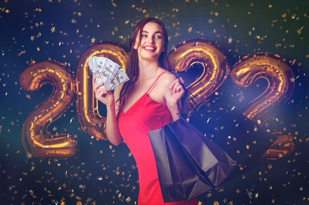 Mulher com dólares e compra confetes de vendas de balões de compras de ano novo na sexta-feira preta