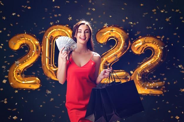 Mulher com dólares e compras ano novo compras vendas de balões pretos sexta-feira comemoram