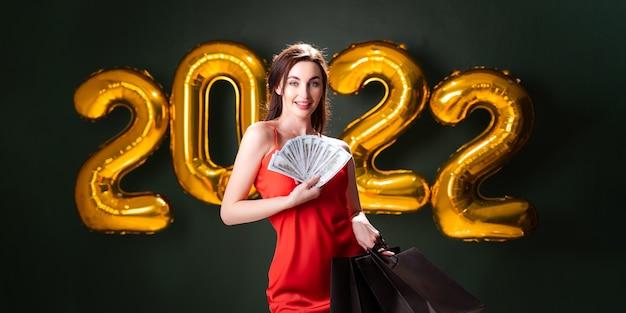 Mulher com dólares e compras de ano novo, compras, balões pretos, sexta-feira, vendas de natal