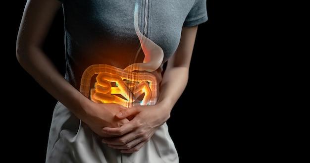 Mulher com dor abdominal, foto de intestino grosso no corpo da mulher, sintoma de diarreia de dor de estômago, cólica menstrual ou intoxicação alimentar. conceito de cuidados de saúde.