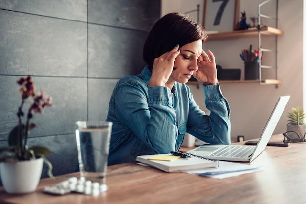 Mulher com dor de cabeça e cápsulas com copo de água em uma mesa de escritório