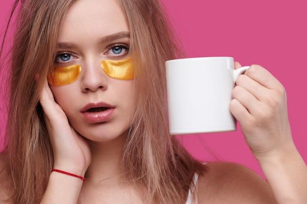 Mulher com dor de cabeça e ressaca segurando um copo com bebida quente no fundo rosa isolado