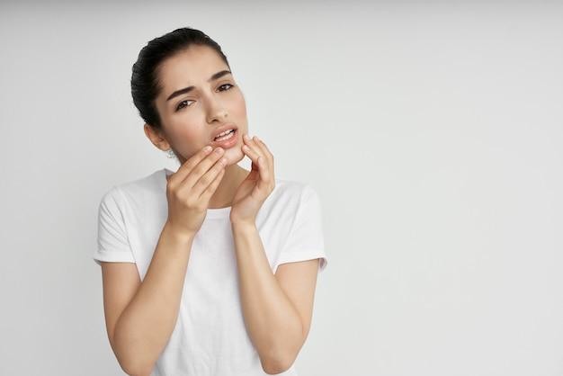 Mulher com dor de cabeça em camiseta branca enxaqueca de estresse