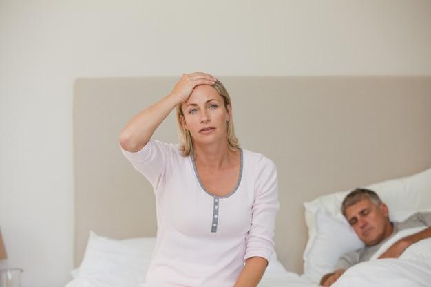 Mulher com dor de cabeça enquanto o marido está dormindo