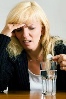 Mulher com dor de cabeça prestes a tomar uma pílula