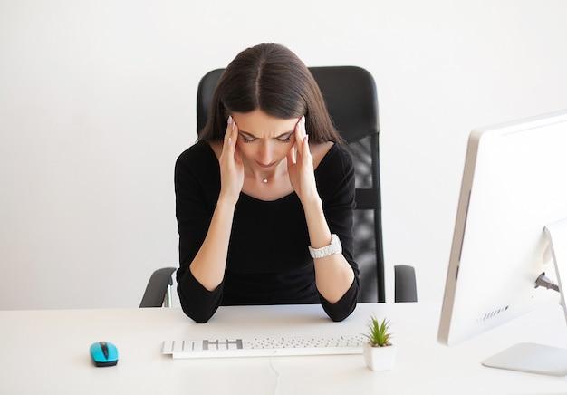 Mulher com dor de cabeça sentada à mesa no escritório