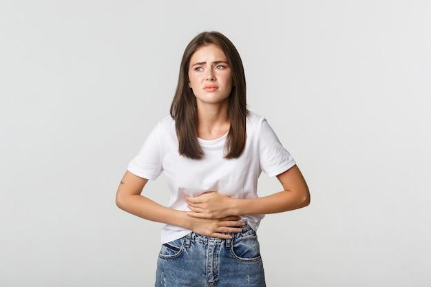 Mulher com dor de estômago, dobrando-se e segurando as mãos na barriga, desconforto de cólicas menstruais.
