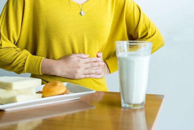 Mulher com dor de estômago e um copo de leite, alergia intolerante aos laticínios, conceito de intolerância à lactose