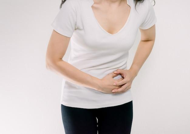 Mulher com dor de estômago mãos segurando o estômago esquerdo.