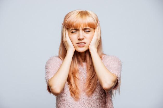 Mulher com dor de ouvido, sentindo pressão, dor de cabeça, isolado. enxaqueca, som alto