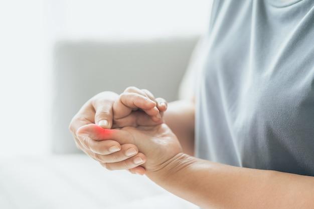 Mulher com dor nas articulações dos dedos e mãos com artrite reumatoide com destaque em vermelho