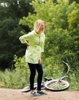 Mulher com dor nas costas e bicicleta caída