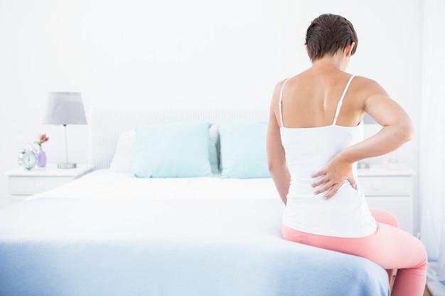 Mulher com dor nas costas em casa no quarto
