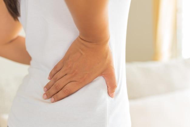 Mulher com dor nas costas feridas. conceito de cuidados de saúde e dor nas costas.