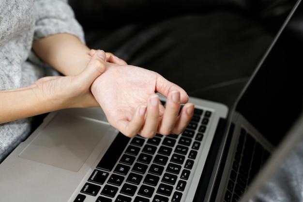 Mulher com dor nas mãos ela está trabalhando no computador